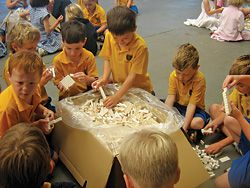 Groups of children assemble the loose pieces into structural elements.