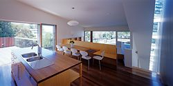 Overview of the living spaces and terrace of the upper level, with views of the tree canopy and surrounding district. Image: Brett Boardman