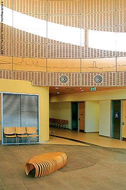 The double-height circular foyer is lit by diffused natural light. The simply etched wooden panels around the perimeter of the foyer illustrate pre-European life including significant historical events of the Port Augusta region.