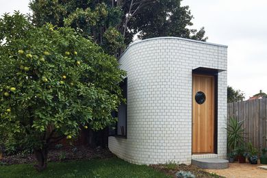 The pavilion references the forms and materials of the Art Deco home that it's tucked behind.
