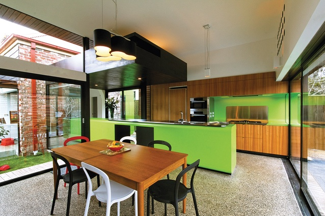 An elongated kitchen bench penetrates the compressed circulation space.