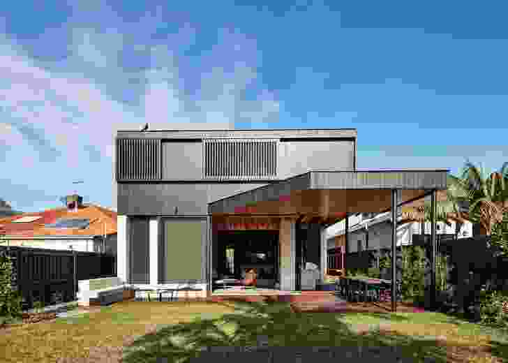 """The rear elevation reaches out into the backyard, with a """"covered garden room"""" extending into a deck area."""