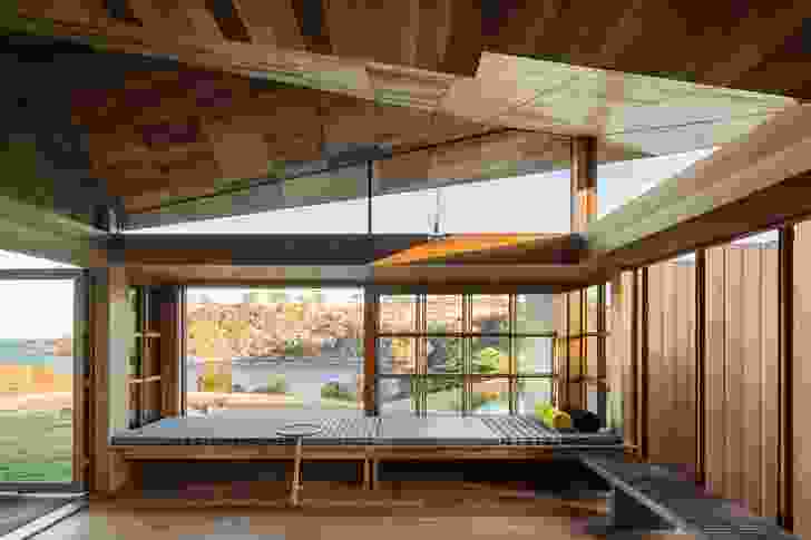 """In the living room, a window seat looks over the """"blessed ancient landscape"""" through broad, multipaned windows that can completely slide away."""