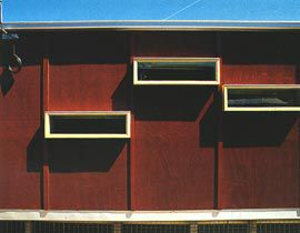 """Facade detail showing the """"box-like"""" cladding and deep reveals."""