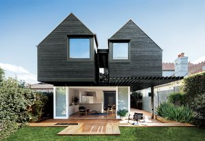 Twin first-floor pavilions and ample openings connect the house to the garden and sky.