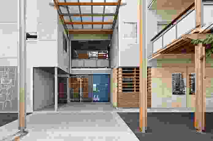 Street-level access to the project. The material palette includes rammed earth, cypress pine, concrete block and compressed fibre cement.