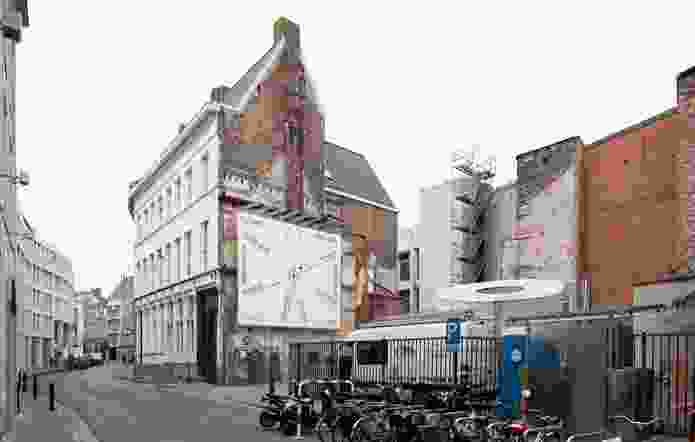 The new wing for Design Museum Gent will be built on a derelict site currently home to a giant toilet paper roll sculpture that houses toilets.