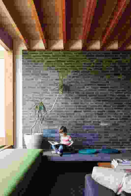 "Textured black bricks form the backdrop to the living area. The space feels ""dug in"" and is created as a ""place for hunkering down."""