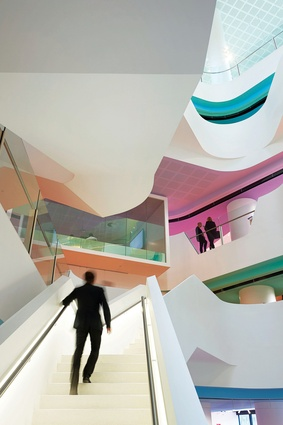 The bold use of pastel colours on each floor and ceiling reduces the scale of the atrium.