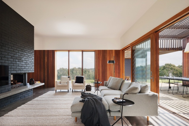 The living room opens to an outdoor kitchen and dining area, sheltered under parallel battens.