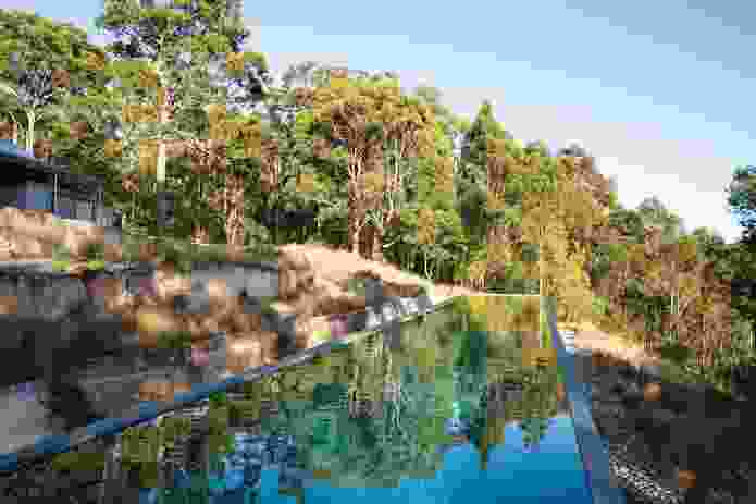 The long rectangular pool sits within a series of terraces marked by sandstone walls.