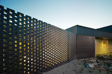 A perforated brick screen shields the northern courtyard from the street.