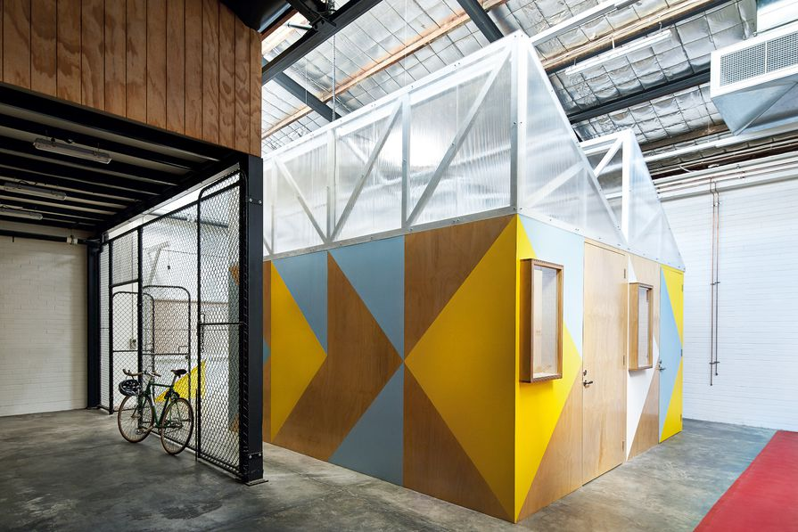 Five small-scale workshop pods act as a tiny precinct within the warehouse space.