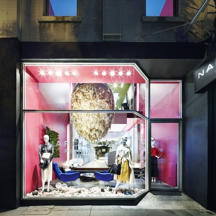 The entry is a shopfront display made inhabitable, with a place to sit and wait, a space for display and a space to be displayed in.