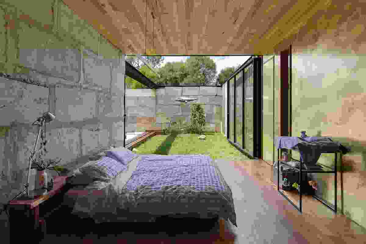 The entire east wall of the bedroom is a glass pivoting door that opens onto the courtyard.