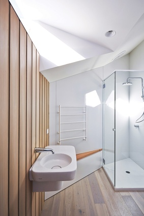 A full-width glazed roof light captures morning sun on the upper-level landing and bathroom.