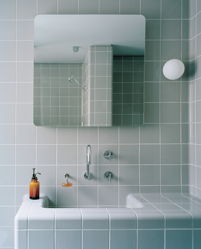 The bathroom's dove-grey, curved tiling and Art Deco bathing alcove evoke a comforting sense of enclosure.