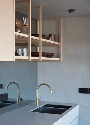 At the rear wall, a large bi-fold door opens to a full kitchen with brass fittings and cement sheet surfaces.
