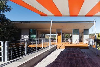 The northern deck features a sunken lounge with a large retractable awning in a wide bright stripe, recalling beach umbrella patterns.