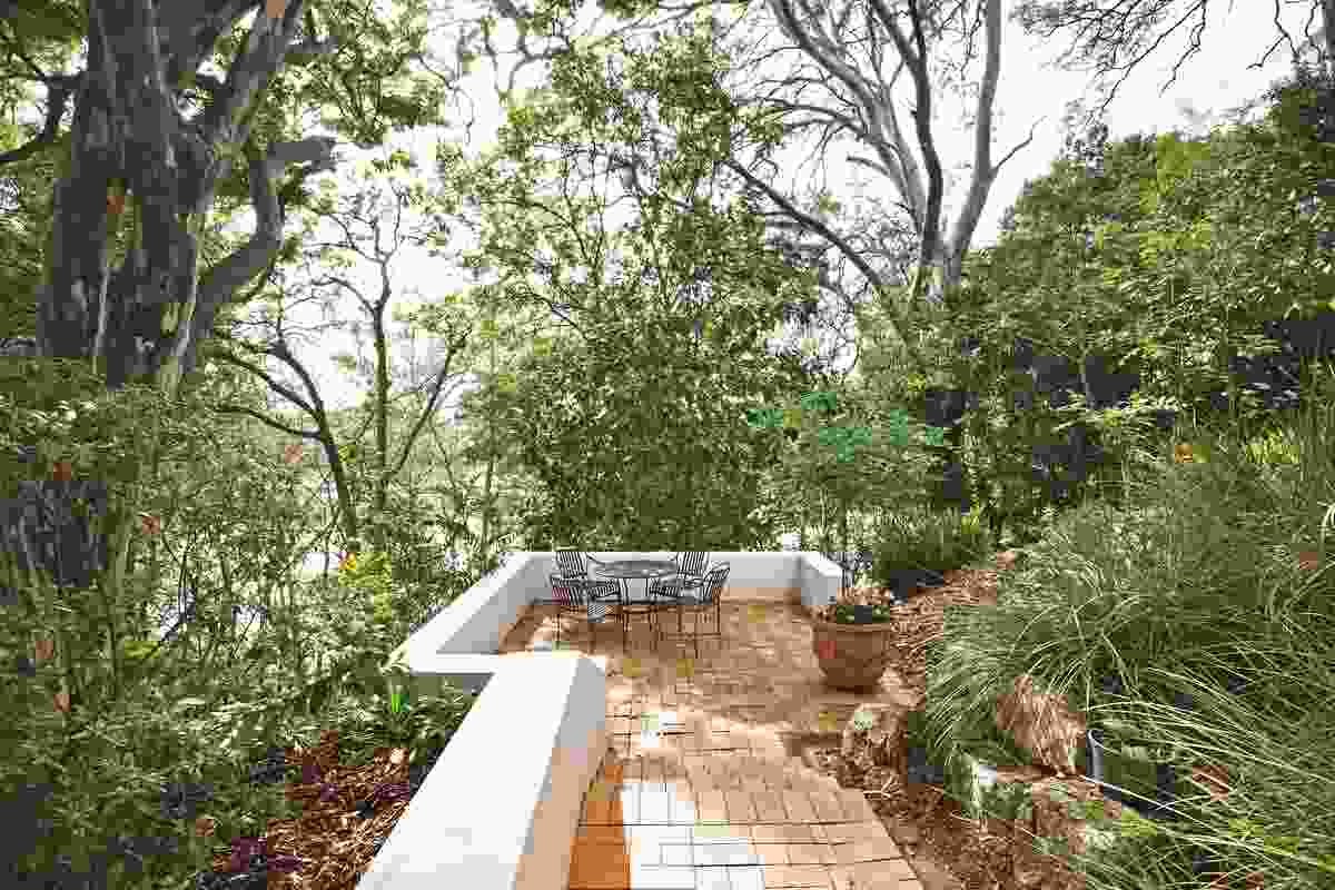 A quiet sitting spot is retained against the hillside, offering views to the river.