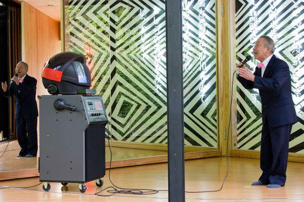 Gombe-san performing at Australia House opening with Karaoke robot.