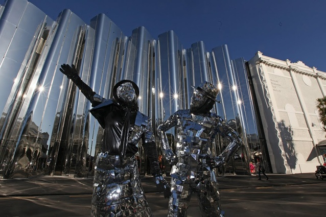 Highly flammable Mirror Man and Mirror Maid pose in front of the Len Lye facade.