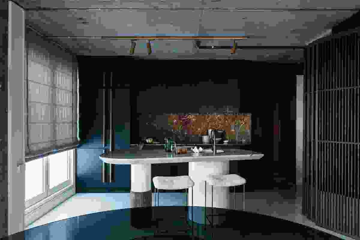 The marble of the kitchen's bespoke island and splashback punctuate an otherwise moody colour palette.
