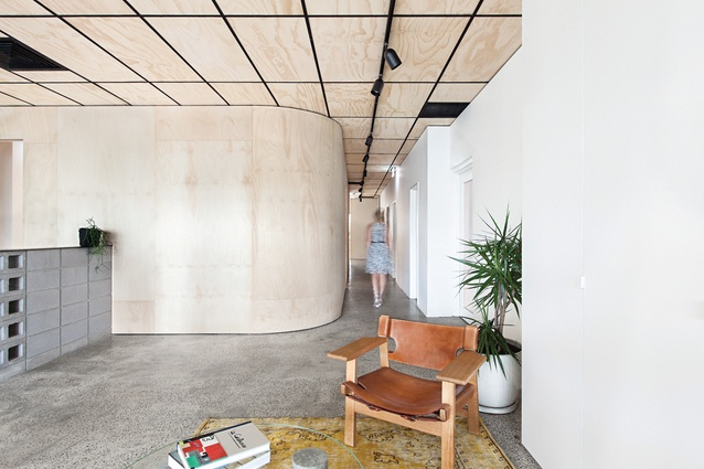 The Bunker houses two companies on the upper level. On entering the building company's side of the office, visitors are greeted with a palette of concrete and plywood.