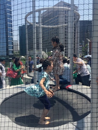 Children enjoy the enclosed public trampolines.