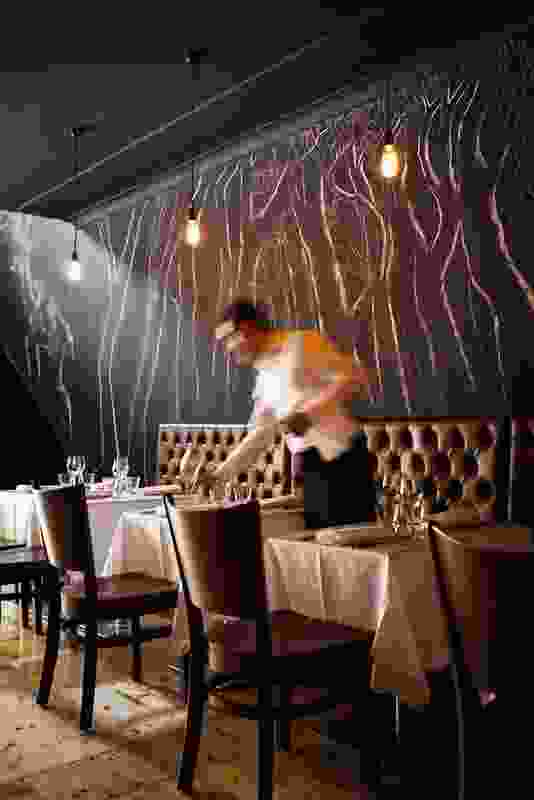 A chalk mural by Nick Hall is drawn behind buttoned leather banquettes.