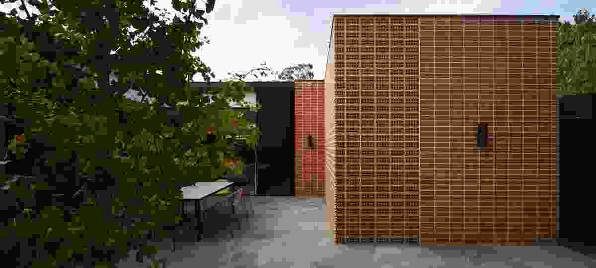 Brick-laid-on-edge brise-soleil screen walls add interest to the courtyard space, while providing fresh air to the garage below.