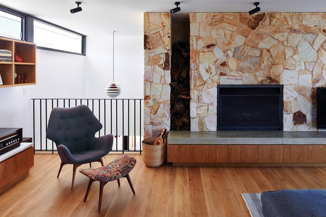 A sandstone feature wall adds nuance to the material palette and continues through both levels of the home.