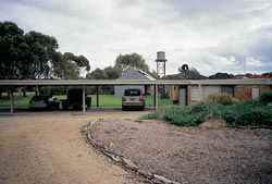 Seen from the approach drive, through the existing carport, the shed appears as another piece of rural infrastructure.