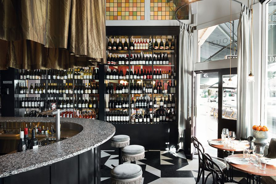 The space is layered with texture and detail, from the speckled terrazzo horseshoe-shaped bar to the tassels on the stools and the monochrome patterned floor.