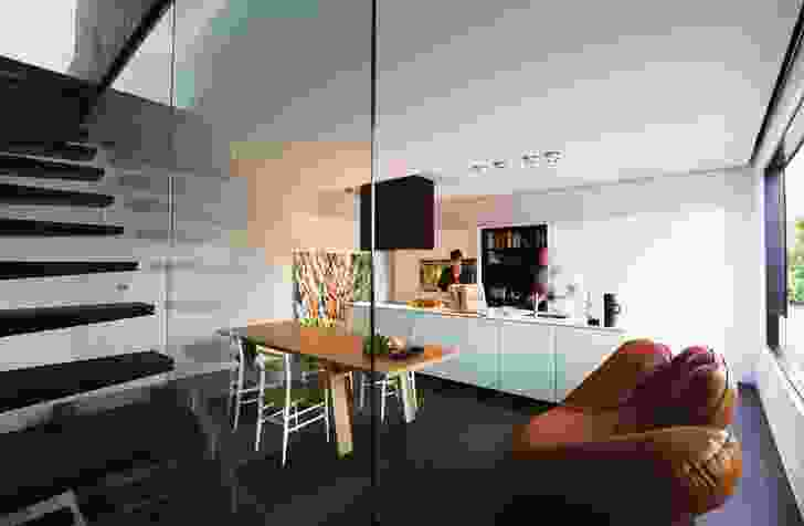 The third floor contains the dining and kitchen area. The kitchen is simple and efficient, with a storage wall along the southern edge. Artwork by Iain Dawson Gallery.