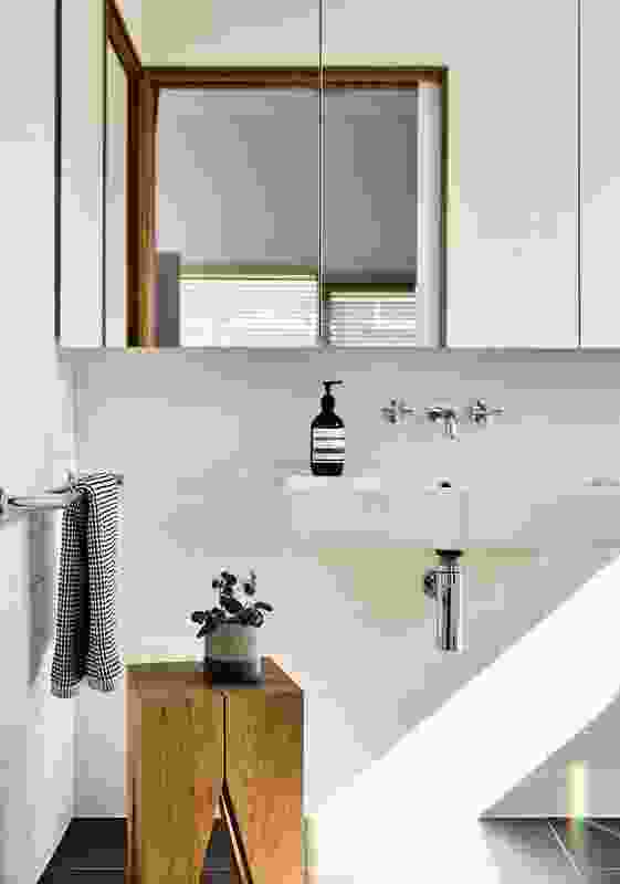 The pared-back palette continues through to the bathroom, with moody bluestone juxtaposed against bright white tiles.