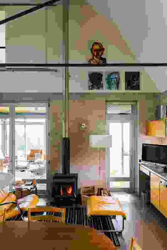 The fireplace reaches up through the exposed roof structure of the double-height dining room. Artwork: Adam Cullen.