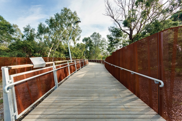 Crafted from sturdy materials, including spotted gum and Corten steel, the bridge is supported by Y-shaped steel columns that minimize disturbance of the ground plane beneath.