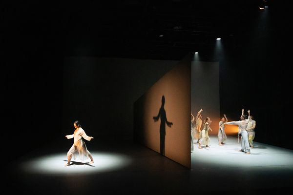 At the start of the performance, a monolithic, wedge-shaped wall slices the stage in two.