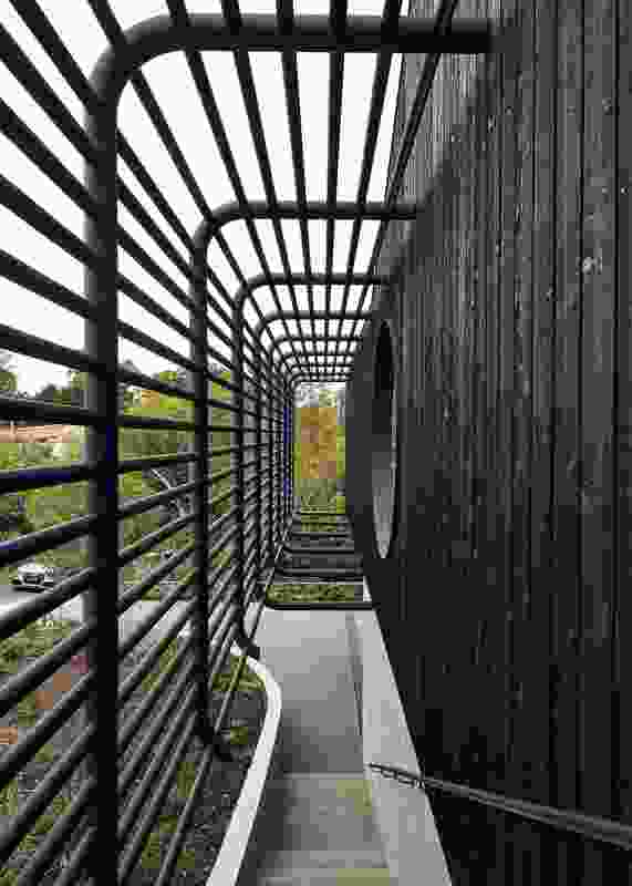 A veil of rolled steel pipes is threaded with blackened timber dowel.