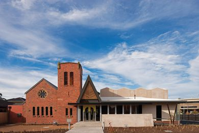 A new concrete wing has been grafted onto the original red brick church.