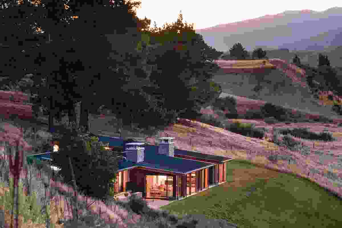 This holiday home near Wanaka steps down the hillside over three levels, with a floating roof plane that follows the contour of the slope.