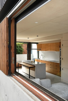 Sliding glass doors beyond the kitchen open to a narrow courtyard that lets in ample daylight.