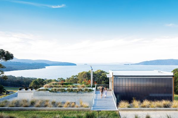The house seems to sit on an axis that bisects the lake, the arc of two headlands, and the horizon of the ocean beyond.