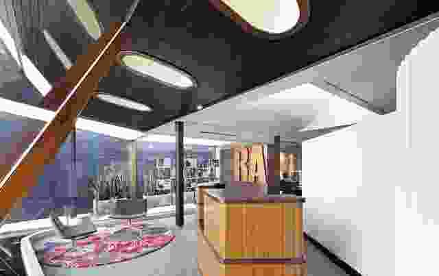 大型椭圆形采光井点缀着入口门厅的木质天花板,照亮了悬挂在玻璃内部的项目图像。