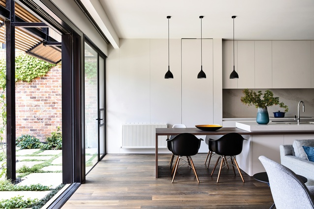The extension's interior is markedly distinct from the existing building, with strong, clean lines of plasterboard running from floor to ceiling.