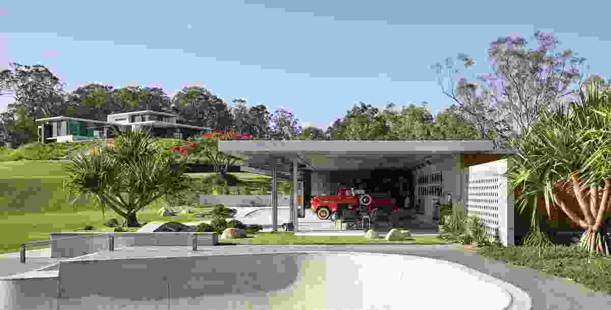A secondary pavilion nestles into the hillside to accommodate a car collection and a workshop.