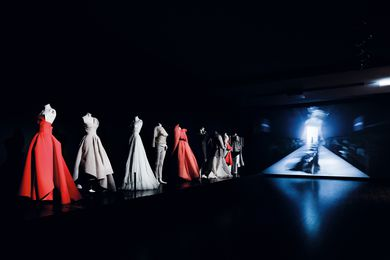Theatrical lighting shines down on the gowns, making them pop in the dark space.