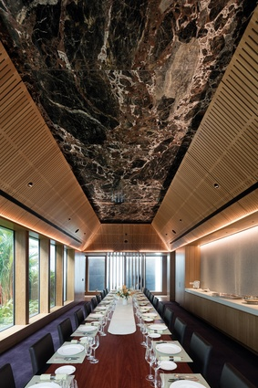 The dining room in the Head of Mission's residence is crowned with Australian Emperador and takes in views of a verdant internal courtyard.