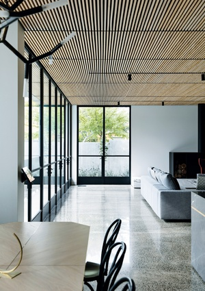 The external face is monochromatic and austere, while the interior is richly textured.